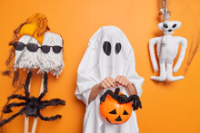 October Holiday. Small Child Dresses Up Strange Costume Decorates Home With Spiders And Spooky Toys Holds Carved Pumpkin Celebrates Halloween Poses Against Orange Background Believes In Evil Spirits