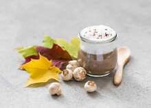 Autumn Dish, Mushroom Cappuccino, Champignon Cream Soup With Milk Foam In A Glass Jar With Maple Leaves On A Light Gray Background