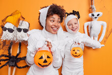 Happy Carefree Mother And Daughter Prepre For Halloween Celebration Hold Two Carved Pumpkins Pretend Being Spooky Ghosts Look Cheerful Pose Near Scarying Toys. Celebration And Party Concept.
