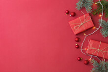 Flat Lay Frame With Fir Branches, Christmas Baubles Decoration And Gift Box On A Red Background