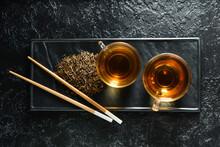 Glass Cups Of Tasty Hojicha Green Tea On Black Background