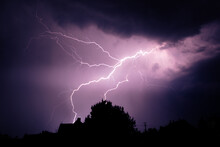Multiple Lightning Strikes Painting The Sky Purple On A Summer Evening During A Thunderstorm