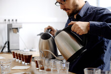 Barista Pouring Water To Coffee Cups