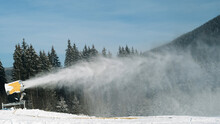 Snow Cannon At Ski Resort In Winter Sun Day. Snowmachine Produced Artificial Snow At Evergreen Spruce Forest, Blue Sky. Preparation Of Ski Track In Mountain Active Sport. Turbine Sprays Water In Cold