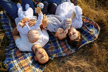 Family With Small Children Lie On A Blanket Among The Tall Grass