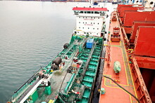 Bunkering Operations At The Port. Bunker Barge Alongside Of The Vessel. Port Of Vostochnyy. Russia, December, 2020.