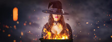 Halloween Witch With A Cauldron. Beautiful Young Woman In Witches Hat Conjuring, Making Witchcraft. Over Spooky Dark Magic Forest Background. Wide Halloween Party Art Design.