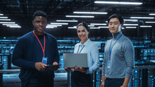 Diverse Team Of Data Center System Administrators And IT Specialists Use Laptop And Tablet Computers, Smiling On Camera. IT Engineers Work On Cyber Security Protection In Cloud Computing Server Farm.