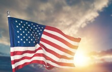 United States Flag Waving On The Wind In Front Of Sun And Blue Sky