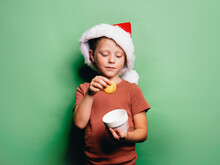 Small Boy In Santa Hat With Sweet Cookie
