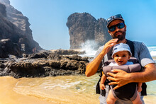 A Young Father With His Baby In The Roque Del Moro Of The Cofete Beach Of The Natural Park Of Jandia, Barlovento, South Of Fuerteventura, Canary Islands. Spain
