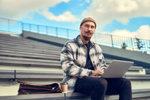 Thoughtful Young Bearded Man With Mustache Works Outisde While Holds Laptop On Legs. Look Sideways