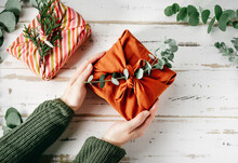 Furoshiki Tissue Wrapping Of Presents. Female Hand Holding A Gift In Eco Friendly Reusable Fabric Package. Small Business, Ethical Shopping Idea. Presents Packed In Plastic Free. Zero Waste Lifestyle