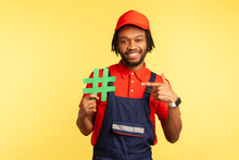 Portrait Of Happy Workman Wearing Blue Overalls Standing, Holding Green Hashtag And Pointing Finger To It, Looking At Camera With Smile. Indoor Studio Shot Isolated On Yellow Background.