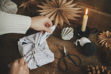 Furoshiki Christmas Gift. Hands Wrapping Christmas Gift In Modern Fabric On Rustic Wooden Table With Scissors, Craft Paper Star, Candle. Atmospheric Moody Time, Nordic Style. Zero Waste Holiday