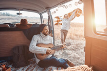 Handsome Young Man Playing Guitar For His Girlfriend While Spending Time In Motor Home