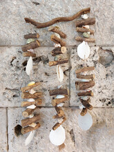 """Traditional Greek Talisman """"wind Chime"""" Made Of Wood And Shells, Hanging On An Ancient Stone Wall"""