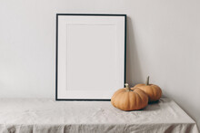 Autumn Still Life. Vertical Black Picture Frame Mockup. Pale Orange Pumpkins On Linen Table Cloth. White Wall Background. Minimal Rustic Interior, Neutral Color. Halloween, Thanksgiving Concept.