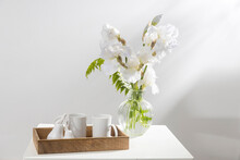 A Bouquet Of Three White Irises And A Fern In A Transparent Vase On The Table. Two Ceramic Tea In The Wooden Tray. Breakfast
