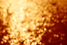 Abstract Holiday Background: Yellow Bokeh Cirles Against Dark Red