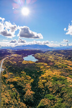 Stunning Fall, Autumn Landscape Shot From Aerial, Birds Eye View. Road Trip, Travel, Vacation, Tourism Shot With Lake, Clouds, Blue Sky And Golden, Yellow Landscape.