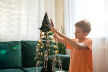 Teen Boy Decorated Halloween Tree For Party At Home. Happy Halloween. Tree Decorated With Halloween Decorations Skeleton.