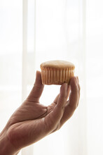 Detail Of A Person's Hand Holding And Showing A Muffin, White Studio Background, Skin Texture And Baked Food