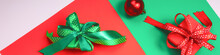 Holiday Composition. Gift Boxes And Christmas Decorations On Red And Green Background, Flat Lay, Top View. Banner
