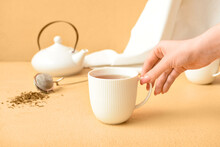 Woman Holding Cup Of Tasty Hojicha Green Tea On Beige Background