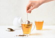 Woman Preparing Tasty Hojicha Green Tea On White Background