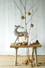 Bare Twigs Decorated With Christmas Ornaments And Wooden Stool With Deer Figurine, Walnuts And Christmas Cookies