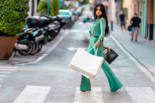 Young Woman With Shopping Bags Walking On Zebra Crossing At Street