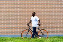 Man Wheeling Bicycle In Front Of Brick Wall
