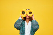 Young Woman Covering Face With Sunflowers In Front Of Wall