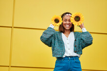 Happy Woman Holding Sunflowers In Front Of Yellow Wall