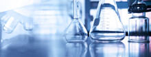 Conical And Volumetric Glass Flask With Microscope And Science Equipment In Chemistry Lab Banner Background
