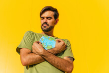 Man With Eyes Closed Holding Planet Earth Illustration In Front Of Yellow Wall