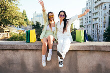 Cheerful Friends With Hands Raised Sitting On Retaining Wall