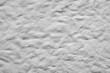 Białe tło z wgłębieniami. Ściana pokryta farbą z widoczną fakturą