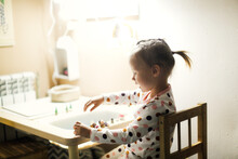Funny Little Toddler Girl Child With A Ponytail In Pajamas Plays At The Table In The Nursery, Independent Games And Earlier Development Of Children