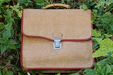 One Old Brown Leather Schoolbag Lies In Green Vegetation And Gray Grass On The Street