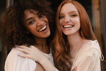 Close-up Of Two Different Races Young Girls With Wide Beaming Smile Are Looking At Camera. Sincerely Joyful Curly-haired Brunette And Long-haired Redhead Are Dressed In Light-colored Clothes.