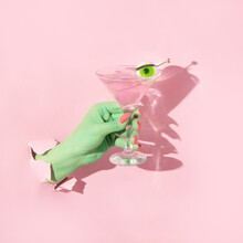 Halloween Creative Layout With Green Witch Hand With Bright Pink Nails Holding Martini Cocktail Glass With Eyeball Against Pastel Pink Background. Aesthetic Season Idea. Minimal Halloween Concept.