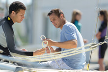 Two Men Sailing A Boat