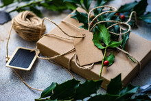 Wrapped Gift Box Decorated With Fresh Holly For Christmas