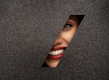 Red Lips Peep Through A Hole In Shiny Black Paper. Beautiful White Teeth