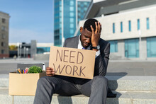 Fired African American Businessman With Paper Poster Saying Need Work And Box Of Personal Things, Sitting Outdoors
