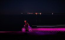 Bicycler Riding Along Sea And Leaving Light Trails At Night