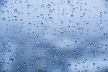 Water Droplets On Glass In Rainy Weather With Small Town Sleeping Areas Out Of Focus In The Background. Autumn Cold Wet Background