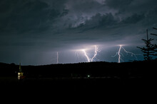 Multiple Lightning Bolts Strike Behind A Hill In The Landscape Of Transylvania, Romania